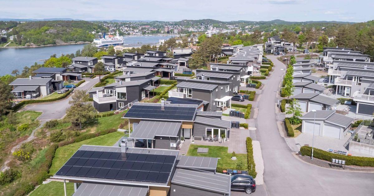 Bildet viser et nabolag med solcellerpaneler på hustakene. Prisen på solceller varierer. Sjekk ditt tak på våre sider.