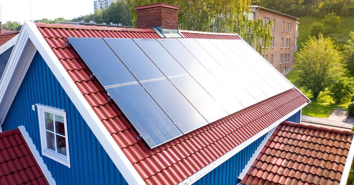 Bildet viser solceller på et skrått hustak. De produserer sin egen strøm hjemme og selger overskuddet.
